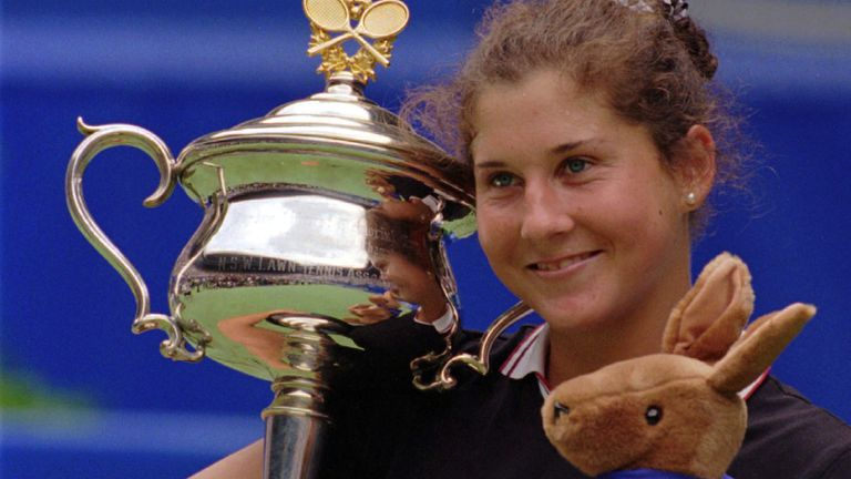 Monica Seles holds the Daphne Akhurst Memorial Cup and a toy Kangaroo in 1996