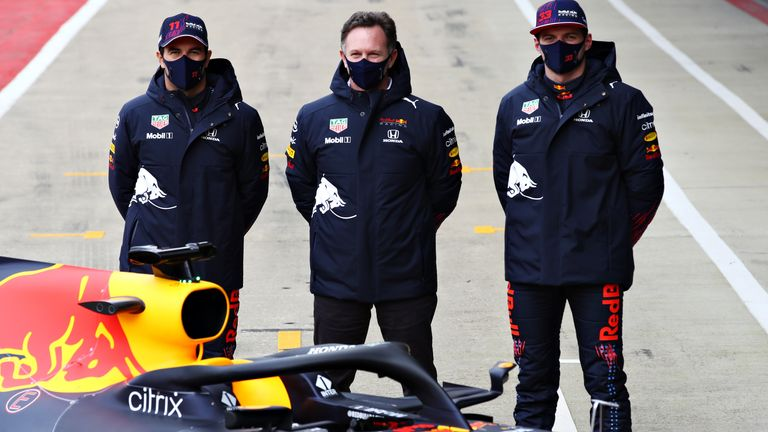 Team boss Christian Horner flanked by his 2021 drivers, Sergio Perez and Max Verstappen, behind the 2019 car in Silverstone's pit lane