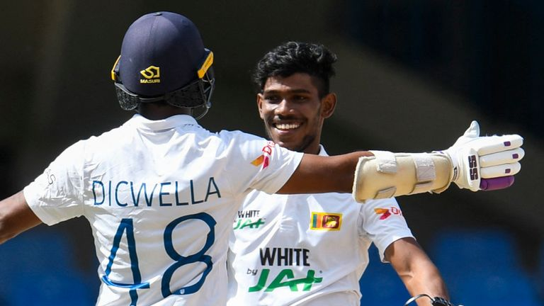 Sri Lanka's Niroshan Dickwella (L) congratulates Pathum Nissanka (R) on reaching his century at the Vivian Richards Cricket Stadium in Antigua