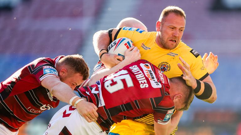 Castleford's Liam Watts is tackled by Wigan's Morgan Smithies, Brad Singleton and Liam Farrell
