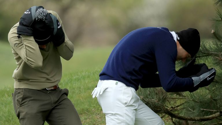 Kaymer and Thomas Detry take shelter from the elements