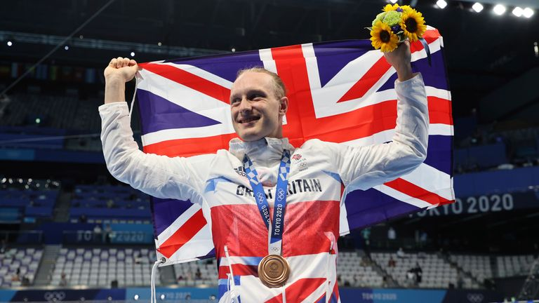 Greenbank raises the Union Jack flag and collects the bronze medal following the men's 200m backstroke final
