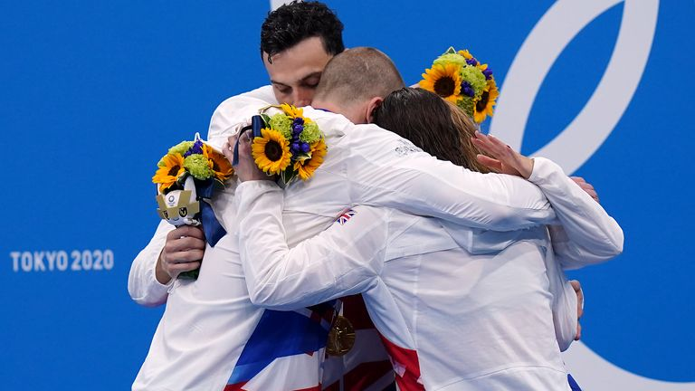 The 4x100m mixed medley team embrace eachother after claiming gold
