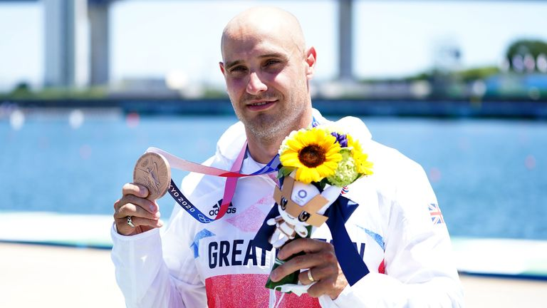 Liam Heath collects his bronze medal on the podium after finishing third in the men's 200m canoe sprint final