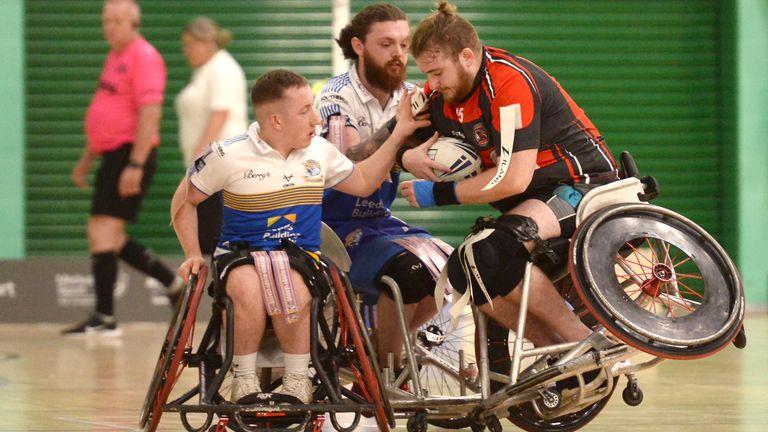 Matt Wooloff of Leyland Warriors battles with Ewan Cibbens  and Nathan Collins of Leeds Rhinos