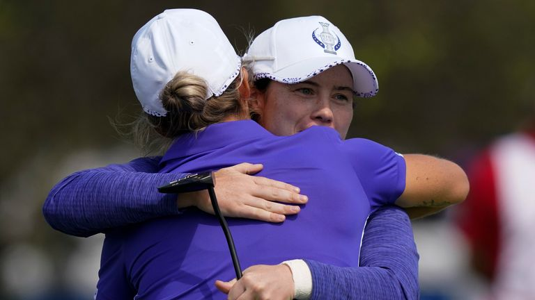 Reid and Maguire hug on the 18th hole after their foursomes win