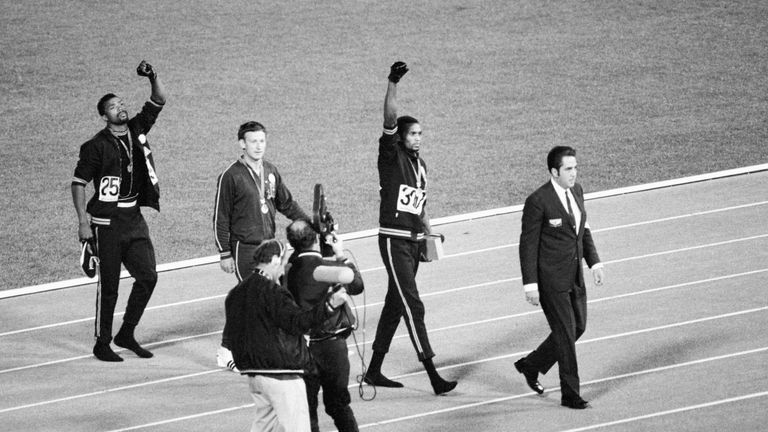Smith (centre) and Carlos (left) continue with their raised gloved hands after walking off the podium in 1968