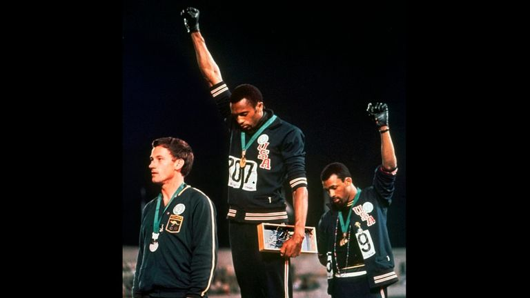 Extending gloved hands skyward in protest, Smith and John Carlos stare downward during the playing of The Star-Spangled Banner